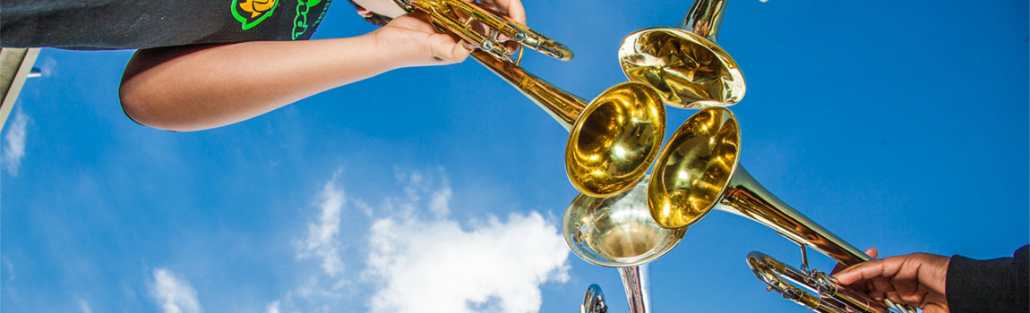 A view from below looking up toward a blue cloudy sky and a circle of four trumpets facing the center