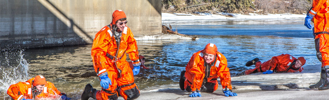 UAF students climb out of the frigid Chena River onto its icy banks during cold water rescue training