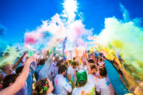 Students throw colored powder in the air during a 5K running event