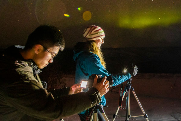 UAF students photograph the aurora on the Fairbanks campus on a winter night.