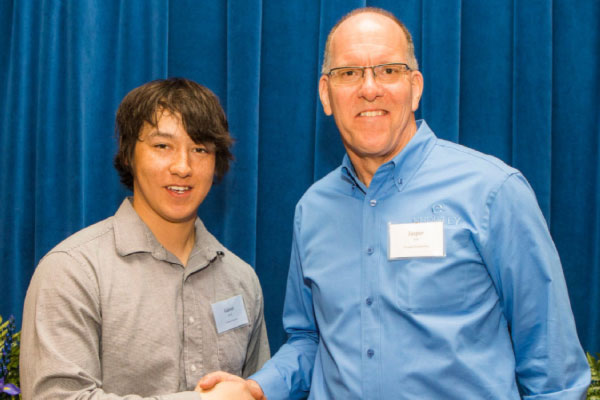 A UAF student shakes hands with a donor who funded their scholarship at the annual UAF scholarship breakfast event.