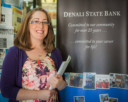 Alumna Betsy Campbell in Business Administration stands by the Denali State Bank booth at the Student Job and Internship Fair. Campbell is now currently the Branch Manager of Denali State Bank.
