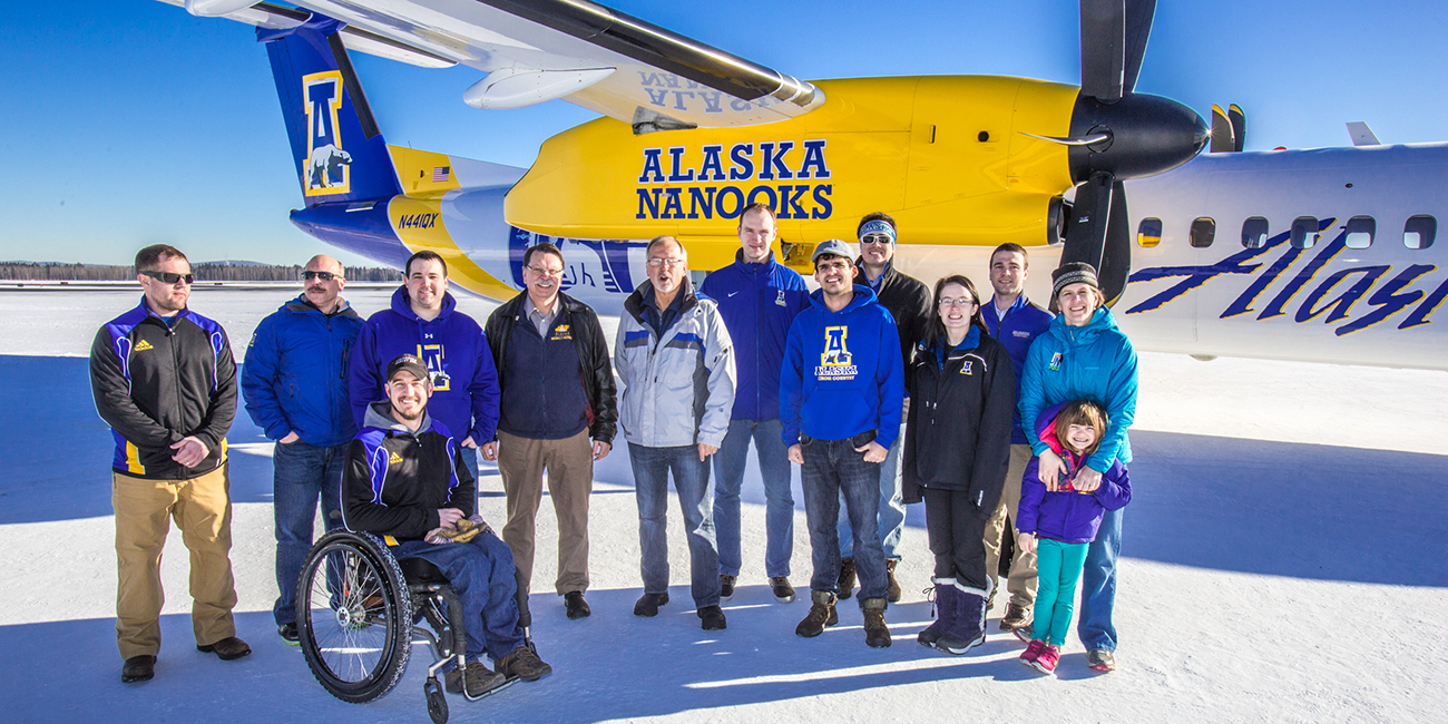 Coaches, athletic department staff members and UAF administrators pose by one of the newest planes in the Alaska Airlines fleet, a Bombardier Q400 turboprop, which features the Alaska Nanooks and UAF.