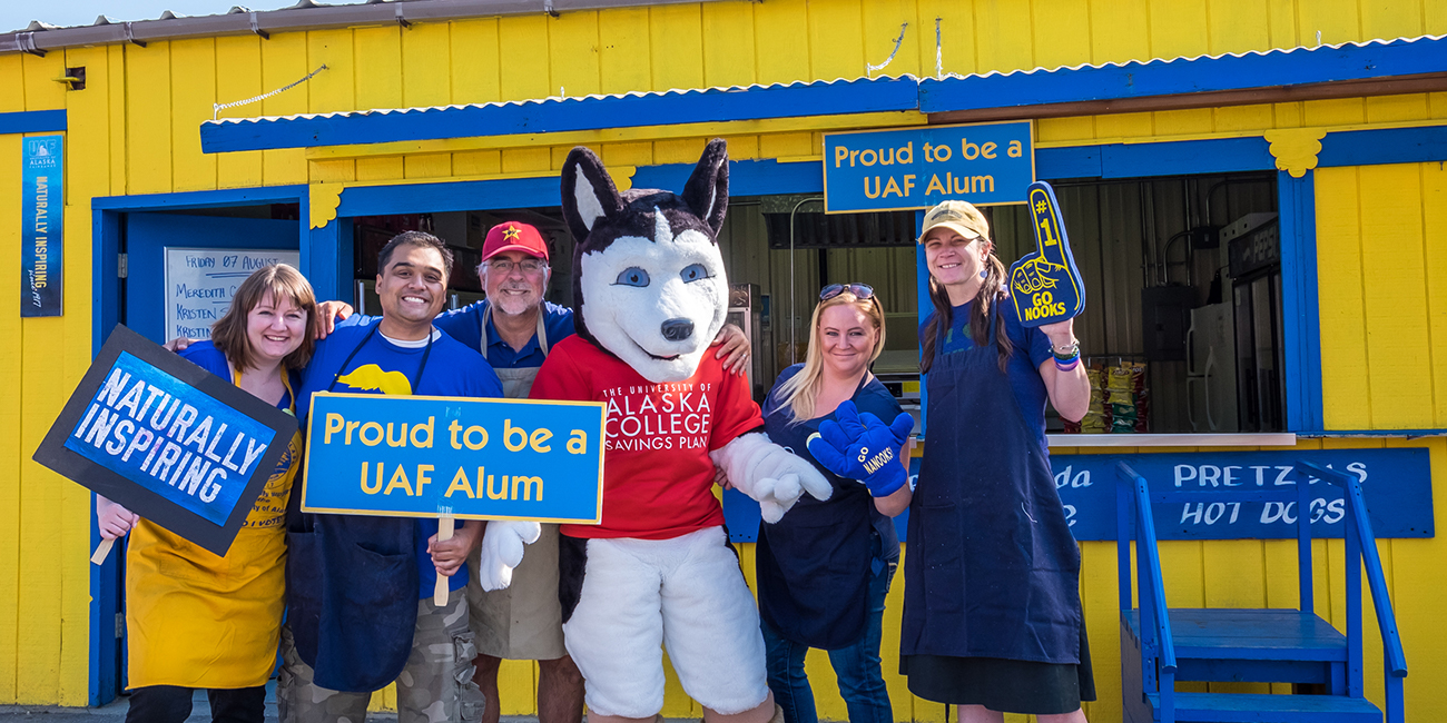 UAF alums Meredith Cameron, Mike Campbell, Todd Paris, Kristin Waggoner and Kristin Sullivan enjoy a visit from Dash the husky during their shift at the Alumni Burger Booth at the 2015 Tanana Valley State Fair.