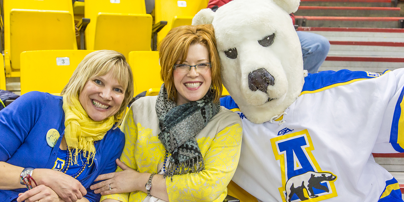 UAF Alumni director Kate Ripley and Development's Emily Drygas found a friendly face in the crowd while watching the UAF-UAA hockey battle in Anchorage's Sullivan Arena.