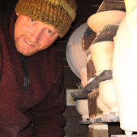 Professor Jim Brashear next to loaded kiln shelves.