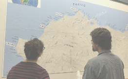 Two people stand with their backs to us, looking at a map of Alaska