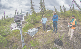 Three people stand on a tundra landscape with research equipment