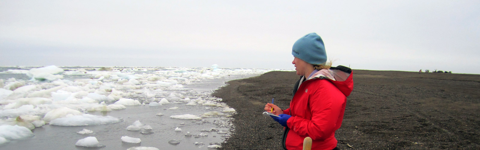 Graduate student observing ice along a shore.