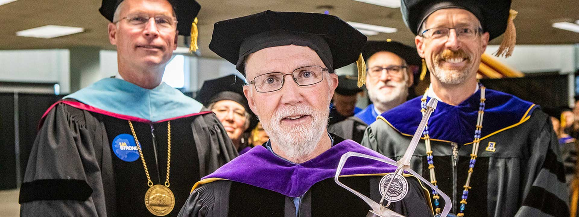 The faculty grand marshall carries the university mace at the start of the 2019 commencement ceremony at the Carlson Center