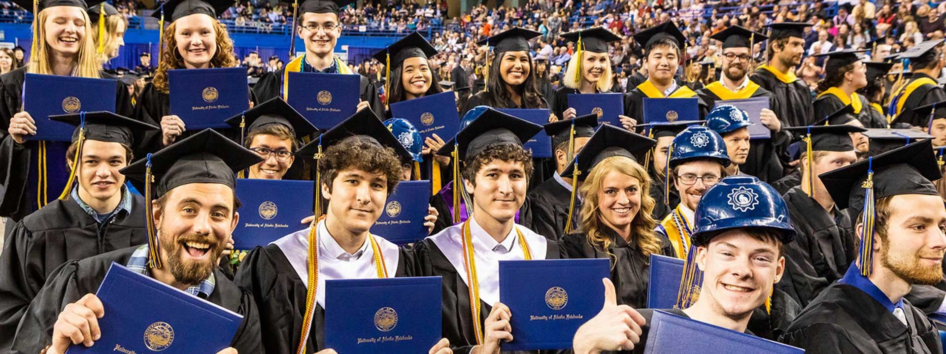Graduates pose with their diploma covers during the 2019 commencement ceremony at the Carlson Center
