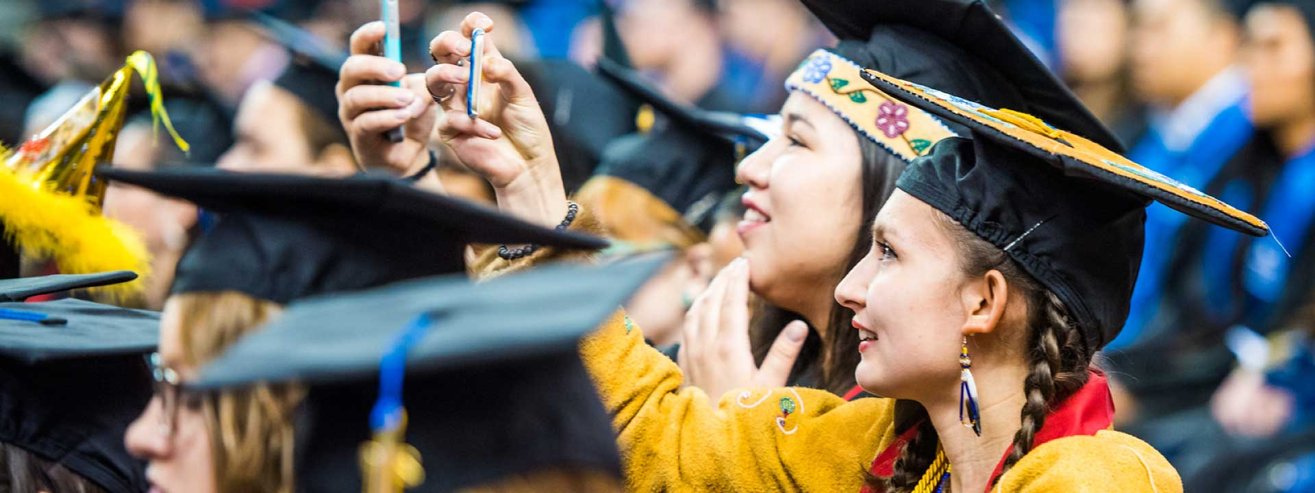 Graduates take selfies at the 2018 commencement ceremony at the Carlson Center