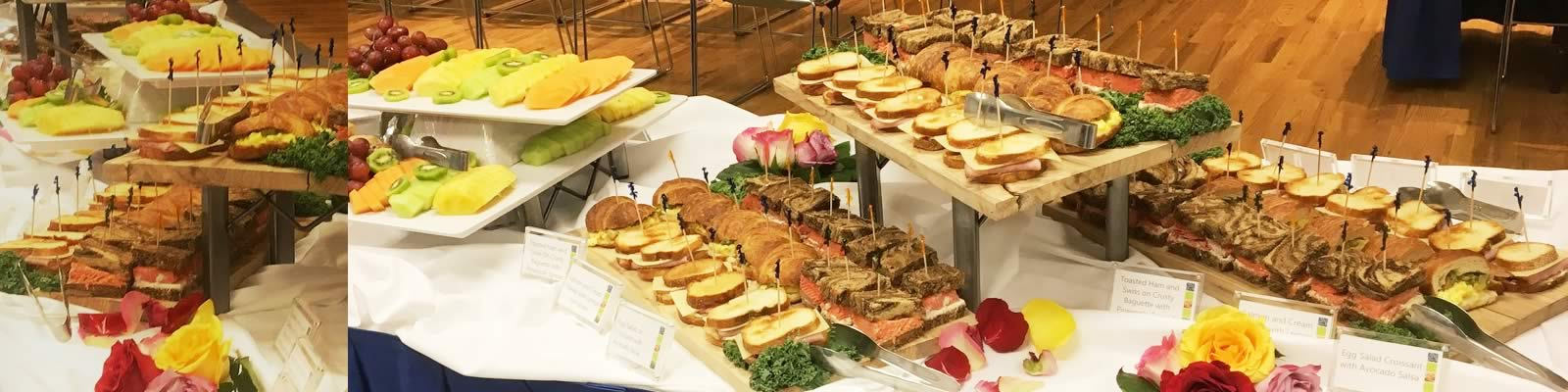 Catered food spread of sliced fruits, sandwiches and flower arrangements