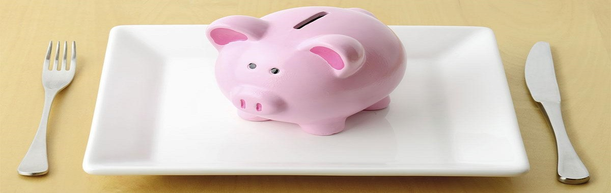 Piggy bank on a white plate with a fork and knife on either side