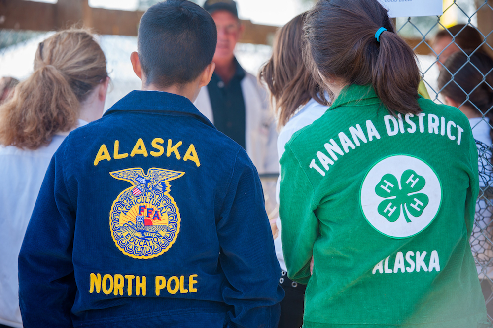 Two youth standing with backs to the camera, one wearing an Alaska FFA jacket and the other wearing an Alaska 4-H Jacket