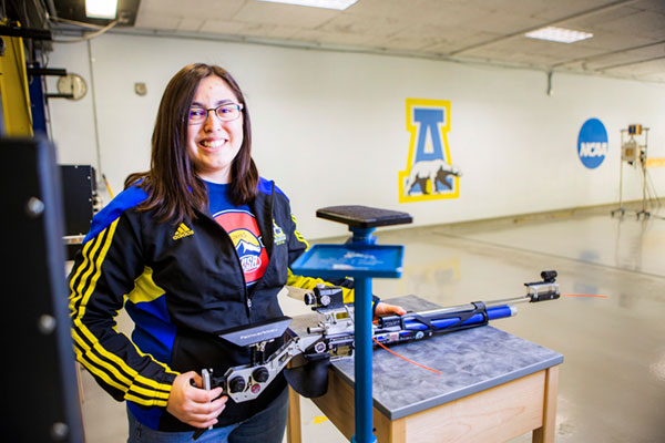 Haley Castillo holds her rifle inside the Patty Center range