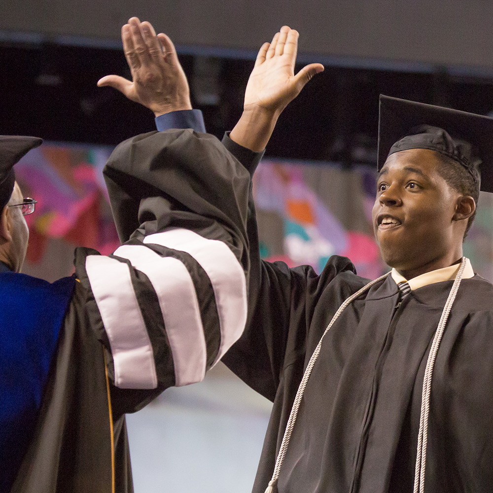 Robert Kinnard III shares a high five with Vice Chancellor Mike Sfraga after earning his degree in justice.