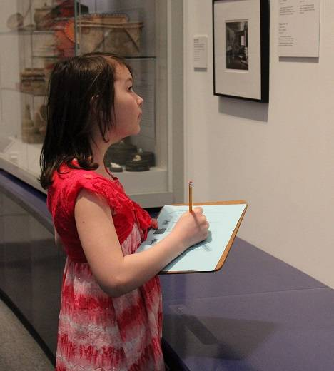 Child with dark hair holding an activity sheet and looking at a museum exhibit.