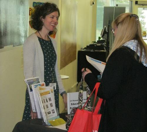 A museum employee talks to a teacher and shows her activity sheets, while they stand in the museum's main hallway.