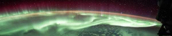 The aurora from space, hovering over the pole in red and green.