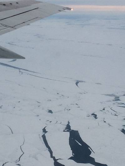 View of sea ice from above. An airplane wing is visible in the upper left.