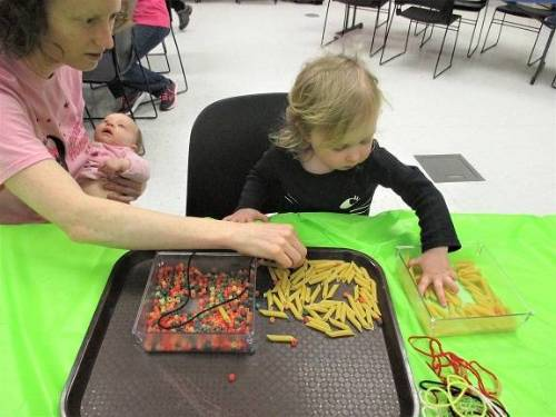 An adult holding a baby sits at a table with a small child, working on a craft project.