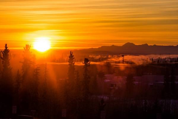 Sunrise in an orange sky, with mountains in the background and trees in the foreground.
