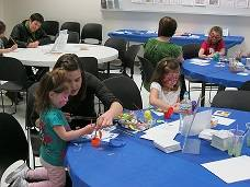 An adult and two children sit at a table, working on an art project.