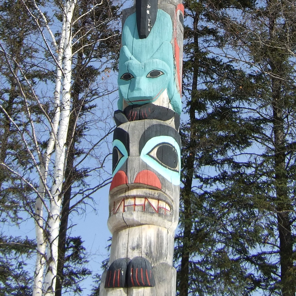 A totem pole carved with a variety of colorful designs, with trees in the background.