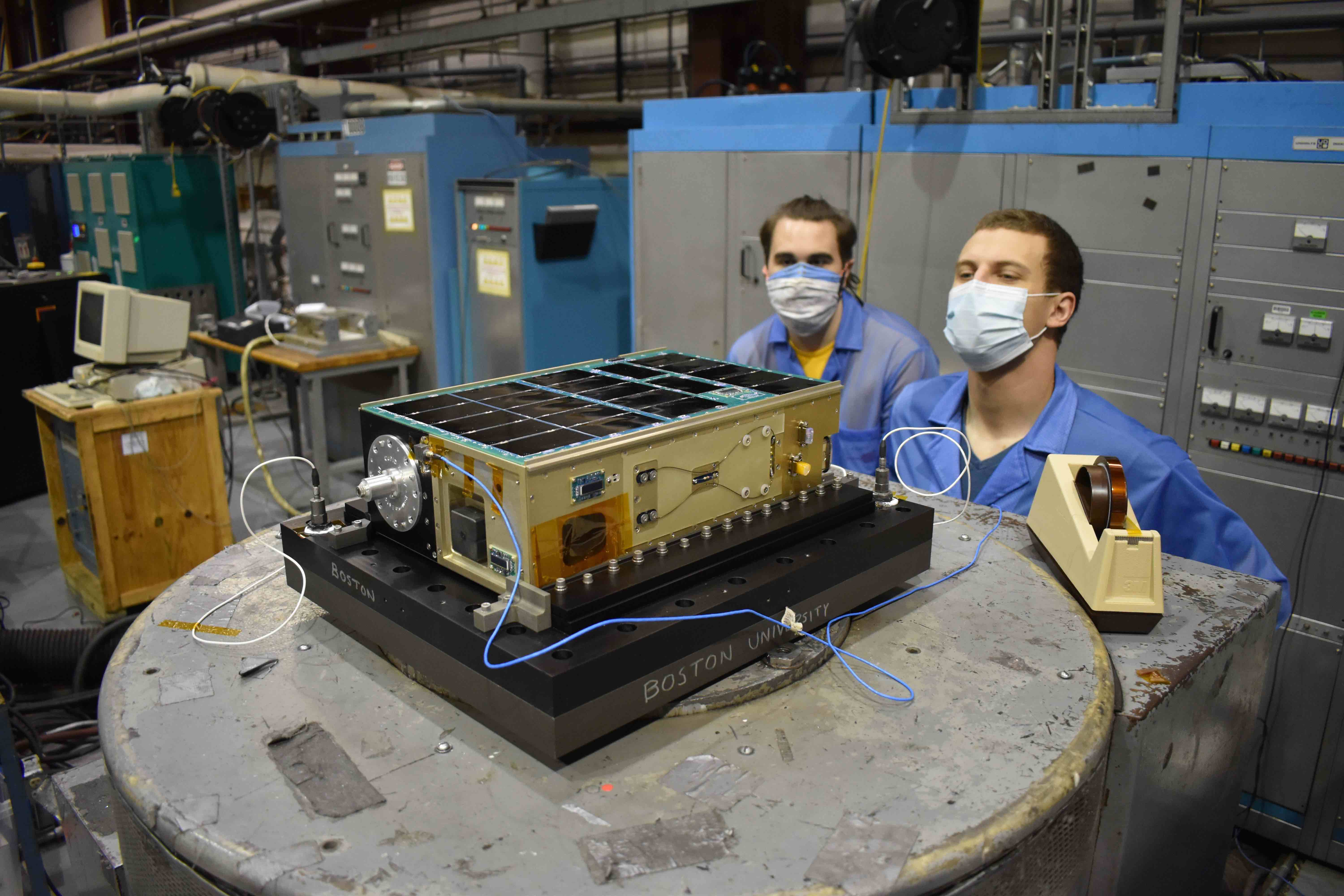 Two men in face masks work on a small satellite, called a cubesat, on a table in a workshop.