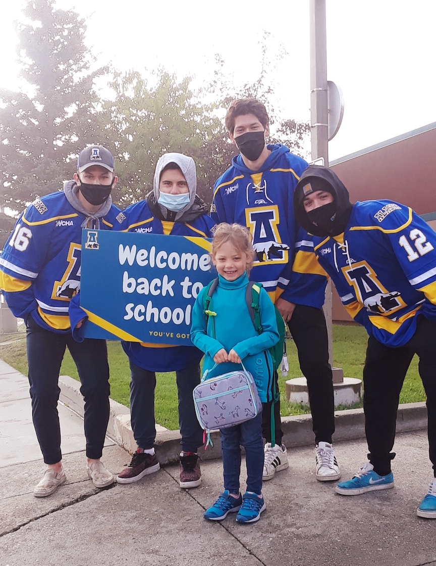 young girl surrounded by UAF athletes