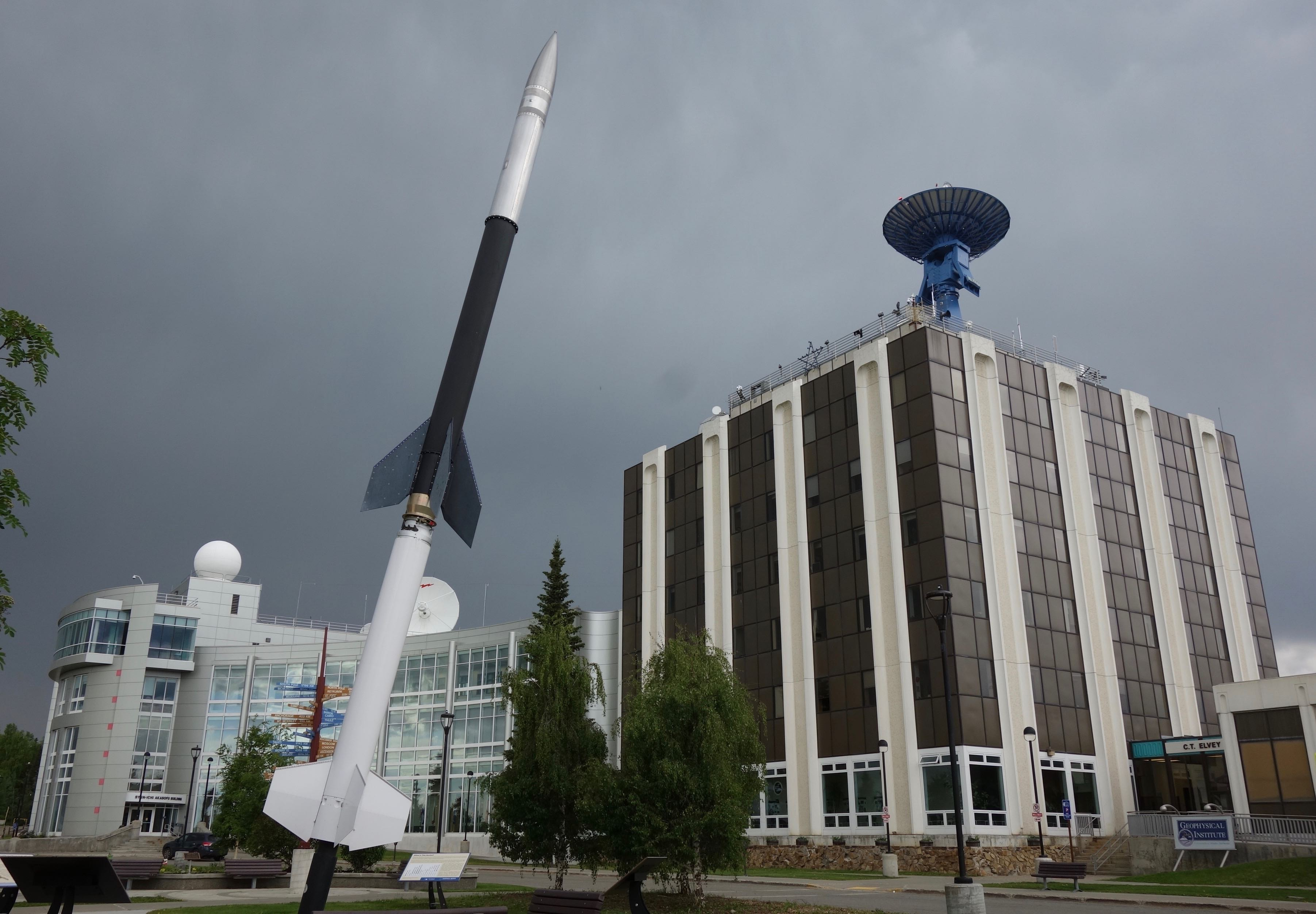 A rocket sits on display on a lawn in front of a seven-story office building with a satellite dish on top.