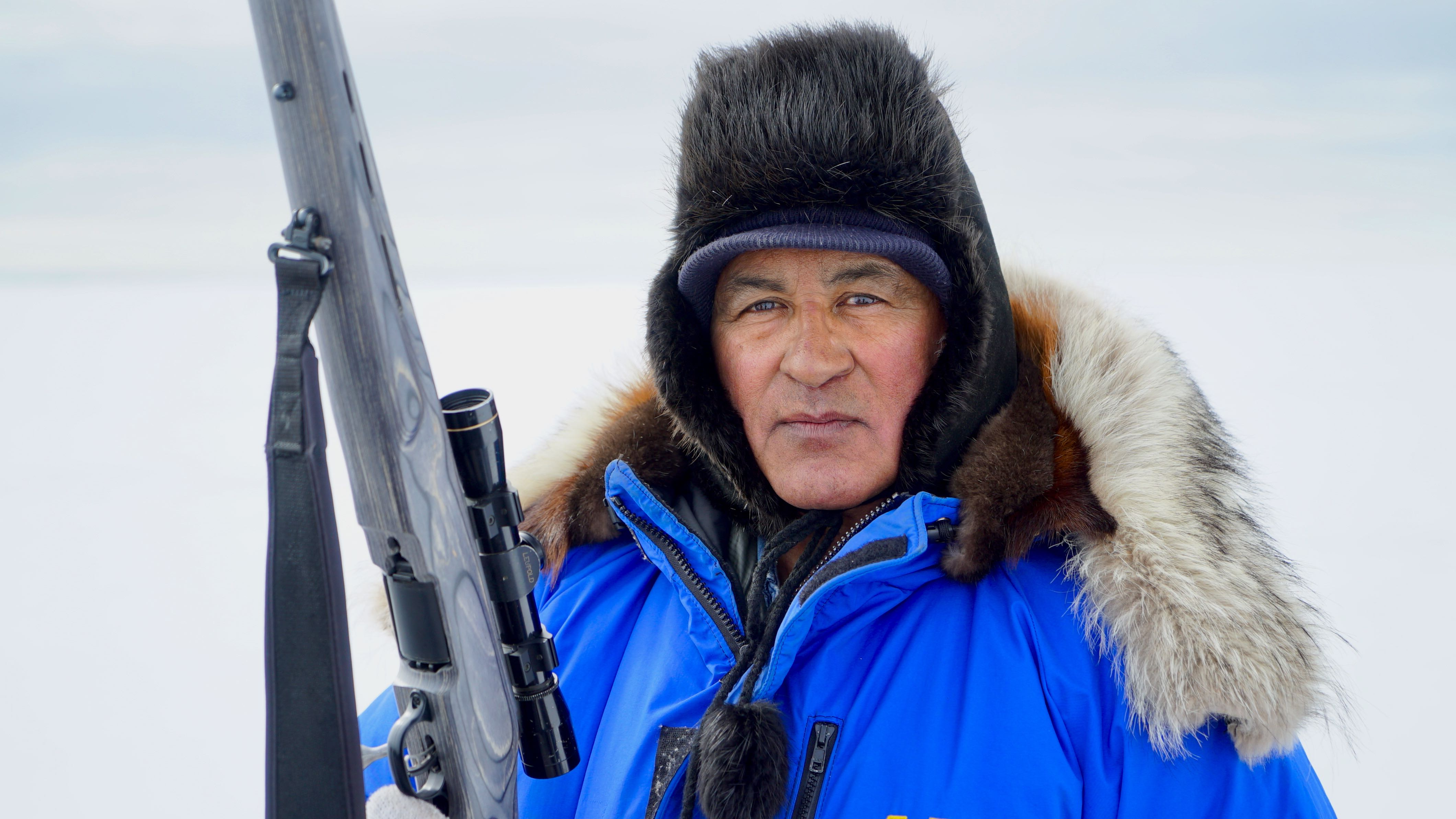A man in winter gear holds a rifle.