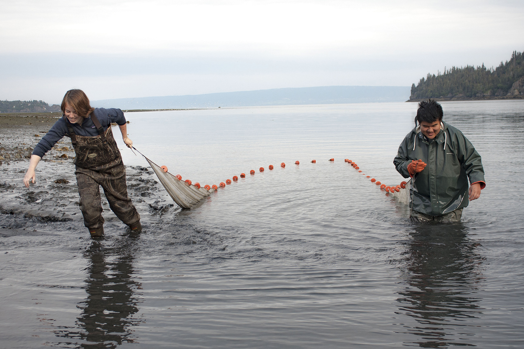 Two people in a river with net
