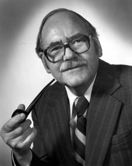 A black-and-white image of a man with glasses and a mustache, smoking a pipe.