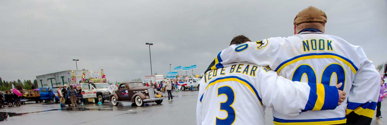 Two people in Alaska Nanooks hockey jerseys embrace at the annual Fairbanks Golden Days parade.