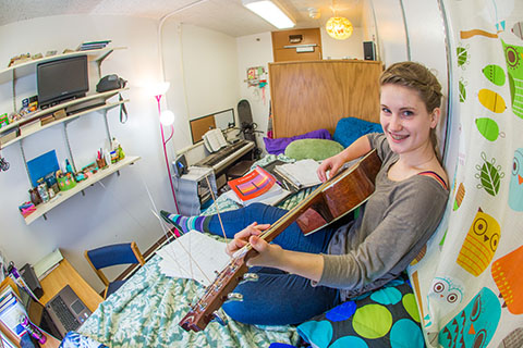 Student playing guitar in a single room