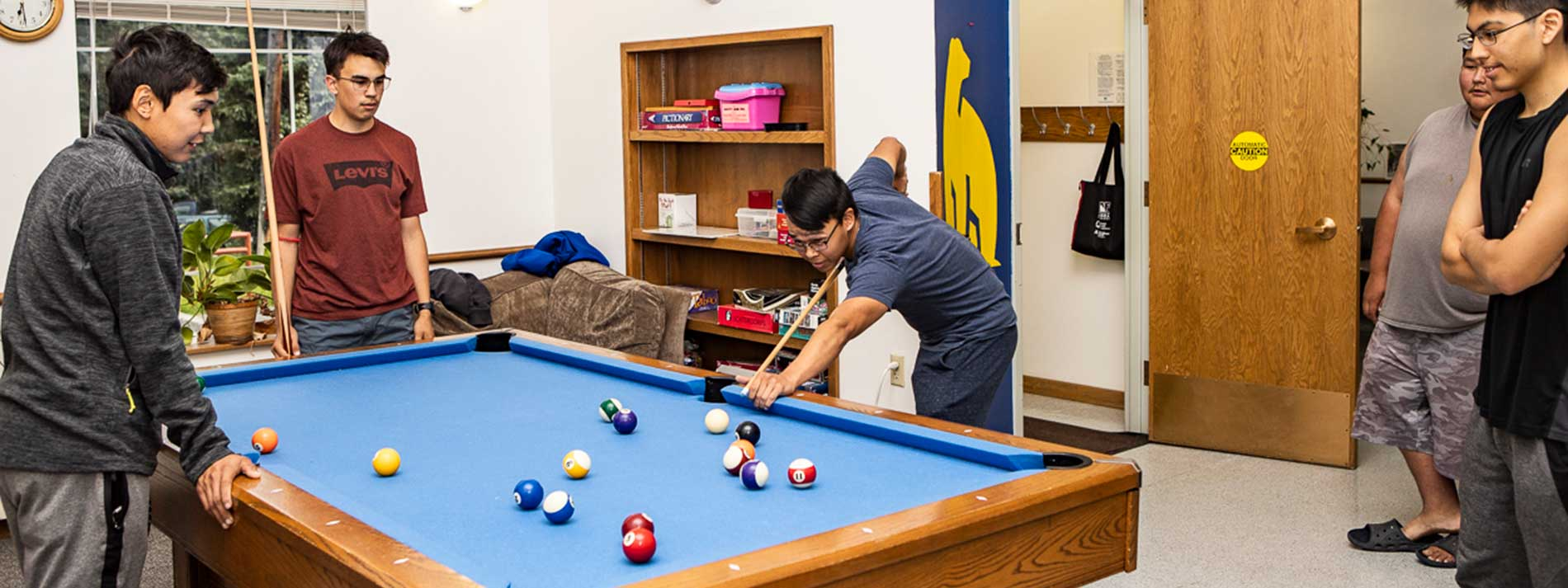 Students play billiards in the Eileen Panigeo MacLean House lounge