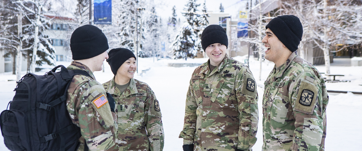 A group of UAF military students visit in front of Wood Center on a winter day
