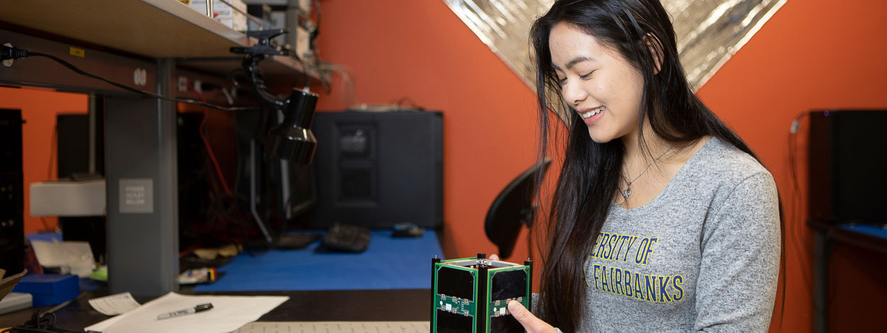 A UAF student holds a cubesat satellite