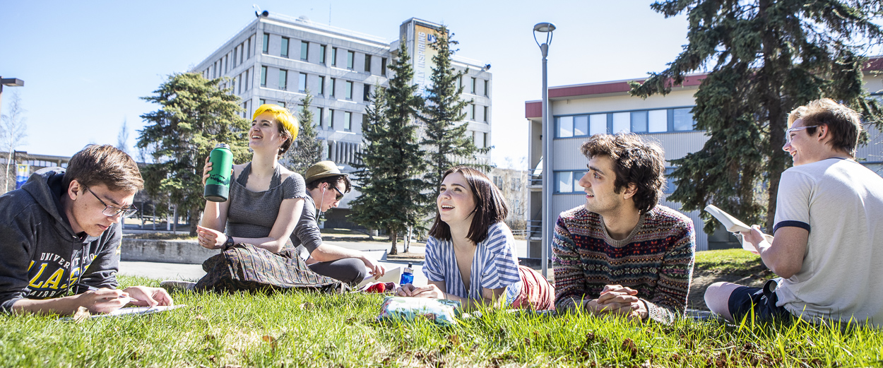 UAF students enjoying the sunshine while studying on the grass outside the Wood Center during the summer