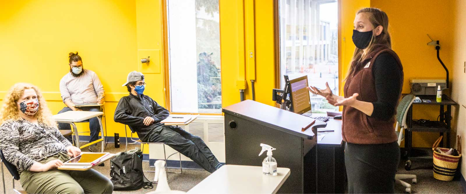 A masked instructor addresses masked and physically distanced students in a UAF classroom