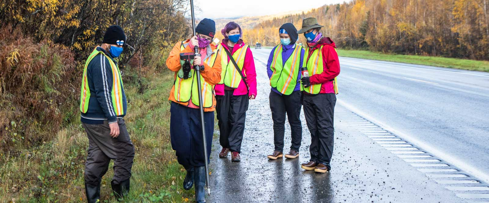 Students in masks and high-visibility safety vests conduct field work at a small landslide on the Steese Highway.