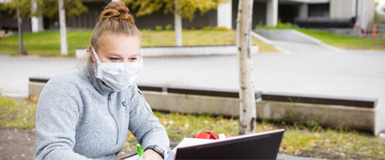 A student wearing a mask sits at a table with a laptop outside the Wood Center