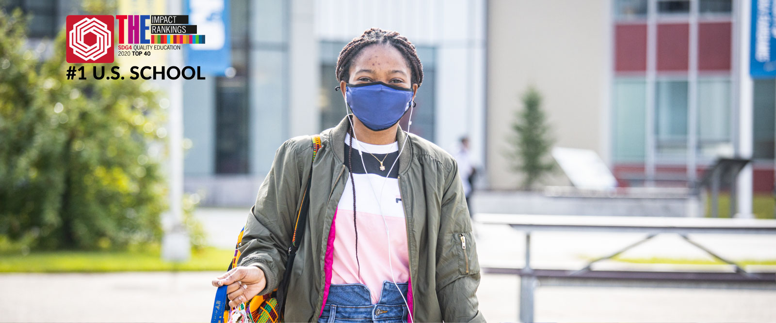 A student wearing a mask walking through Cornerstone Plaza
