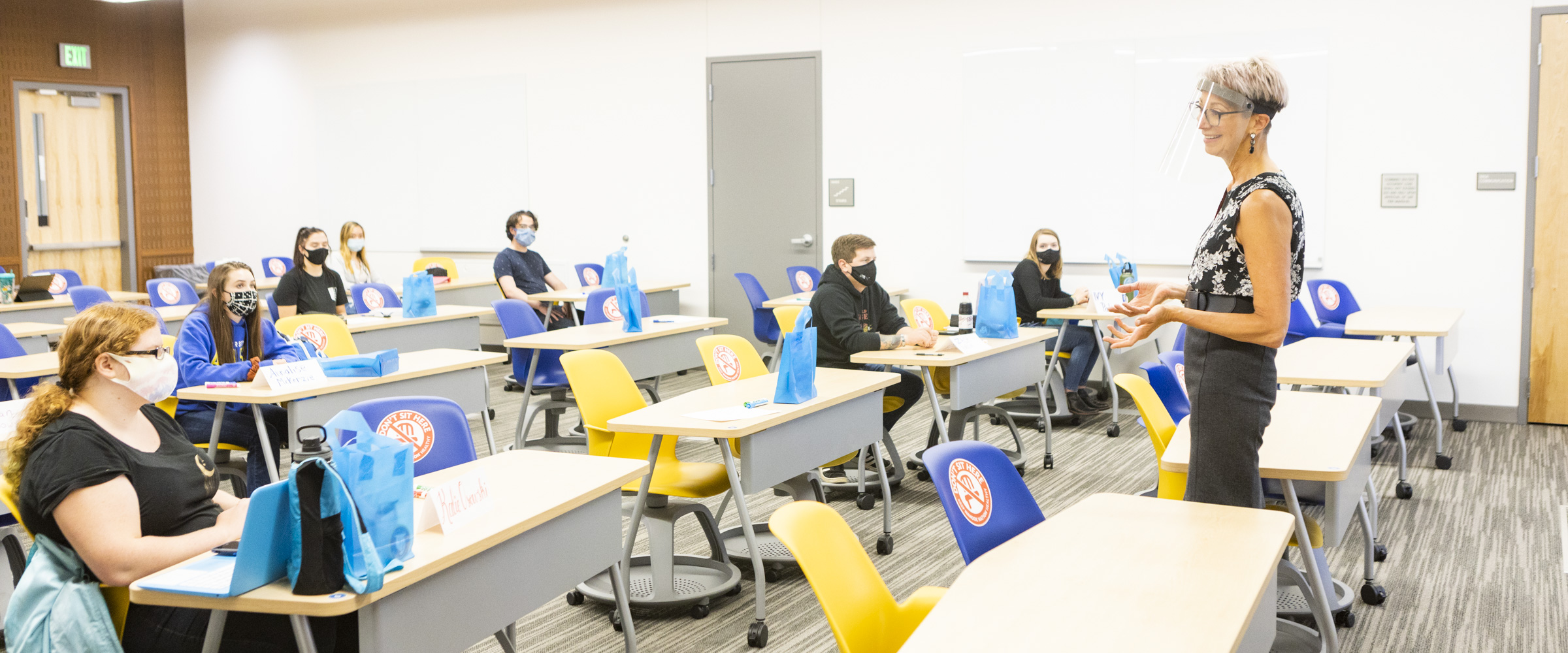 An instructor wearing a face shield addresses a classroom of physically distanced and masked students.