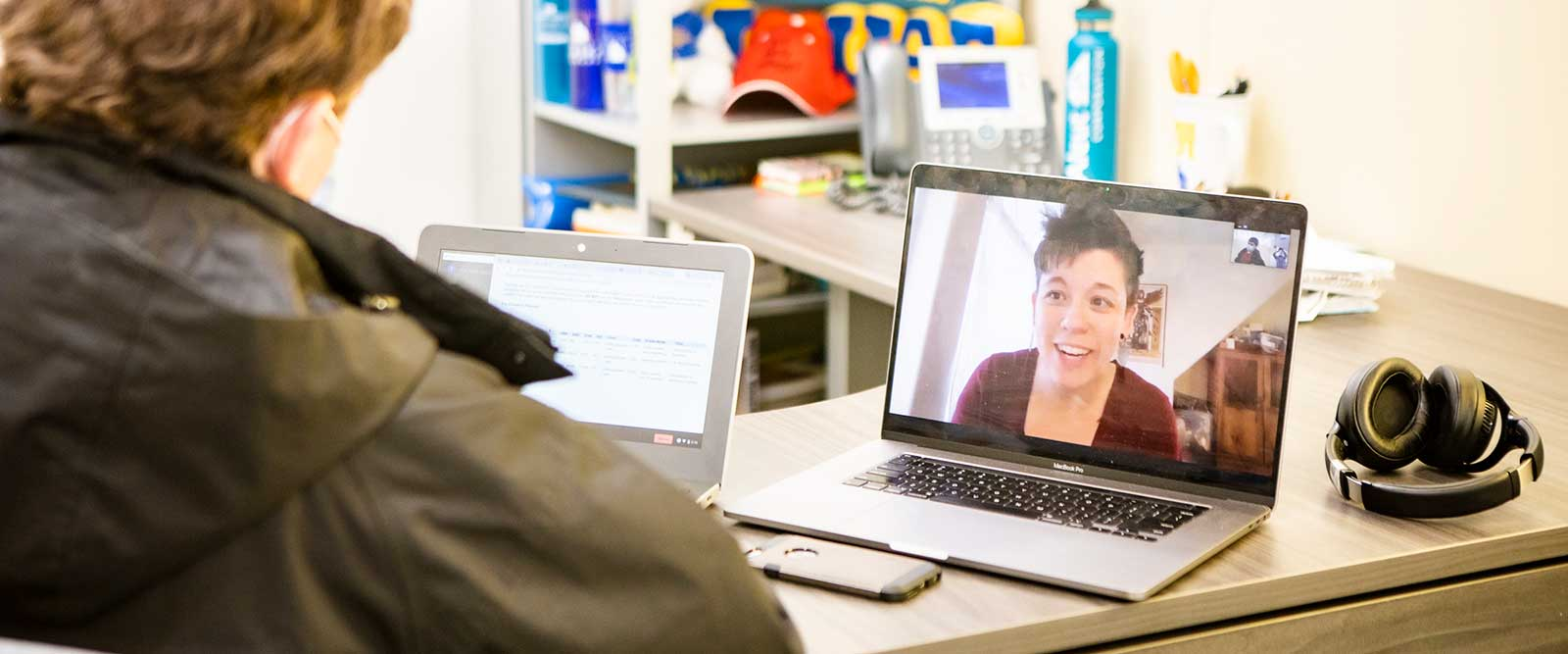 A student on a laptop video conferences with an advisor during a virtual advising session.