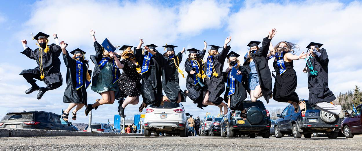 A group of masked UAF graduates in caps and gowns jump outside the Patty Center