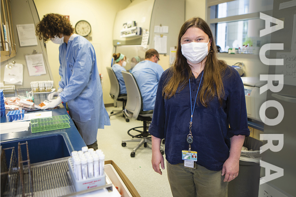 Jayme Parker, facing the camera, stands in a lab and wearing a mask. There are lab workers, vials and equipment in the background.